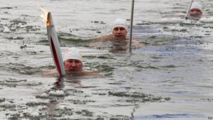 Torchbearer Alexander Brylin swims with the Olympic torch across the Amur River in Blagoveshchensk
