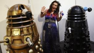 Fan dressed as Tardis poses with Daleks