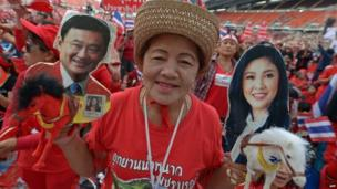 "Thai pro-government ""red-shirts"" hold pictures of Thaksin and Yingluck Shinawatra as they gather at Rajamangala stadium in Bangkok, 24 November 2013"