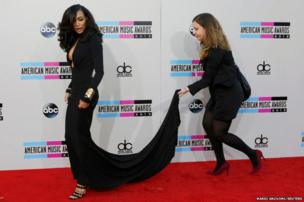 Actress Naya Rivera gets assistance with her dress as she arrives at the 41st American Music Awards in Los Angeles, California