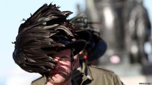 The feathered hat of an Italian Bersagliere is blown by a strong wind