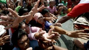 Typhoon survivors jostle for plastic bags of food relief along a road Thursday, Nov. 28, 2013, in Tacloban city, Leyte province in central Philippines.