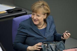 German Chancellor Angela Merkel takes her mobile phone out of her bag during a session of the Bundestag lower house of parliament in Berlin November 28, 2013.