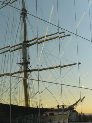 Tall ship reflected in a window