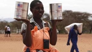 A woman receiving tins of food aid in north-east Zimbabwe - Monday 25 November 2013