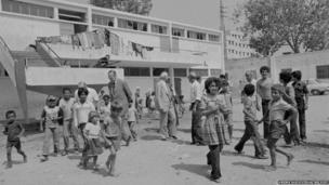 Officials meet crowd of Palestinian refugee children in Jordan (1971).