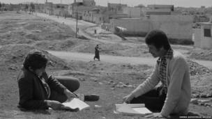 Two students sit with their books at UNRWA's Baqaa Camp