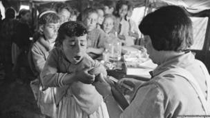 A small girl is vaccinated against cholera by a nurse in east Jordan in 1971