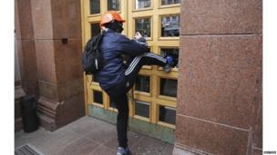 Unidentified man kicks in panes of glass at Kiev City Council 01/12/2013