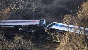 Passenger cars are on their side after a Metro-North train derailed in the Bronx
