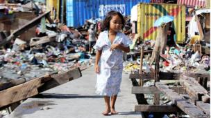 Little girl walks down debris filled street. Photo: Rolan Garcia