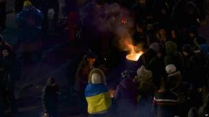 People warm themselves by a fire on Independence Square in Kiev 02/12/2013