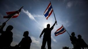 Anti-government protesters wave Thai national flags after they toppled barricades near the Government House in Bangkok, 3 December 2013