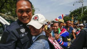 An anti-government protester hugs a riot policeman during a rally near the Government House in Bangkok, 3 December 2013