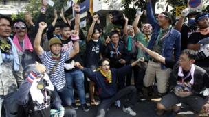 Anti-government protesters pose with riot police during a rally outside the Government House in Bangkok, 3 December 2013