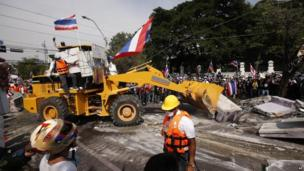 Anti-government protesters use a bulldozer to remove concrete barriers outside the city police headquarters in Bangkok, Thailand, 3 December 2013