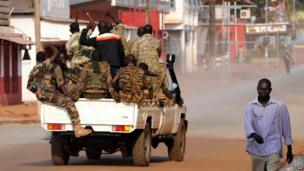 Soldiers raise their fists while on patrol in a street of Bangui on 5 December, 2013