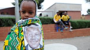 Child draped in cloth with image of Nelson Mandela outside former Soweto home