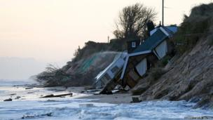 Collapsed houses lie on the beach after a storm surge in Hemsby, eastern England