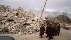 Soviet soldiers look at rubble in the devastated town of Spitak, on December 12, 1988, after an earthquake hit Armenia, on December 7, 1988.