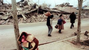 Survivors walk in the devastated town of Spitak, on December 11, 1988, after an earthquake hit Armenia, on December 7, 1988.