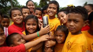 Many hands reach for Queen's Baton during the relay in Nuku'alofa, Tonga.