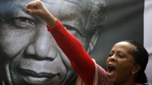 A mourner shouts Viva Mandela by a portrait of Nelson Mandela soon after the coffin of former South African President Nelson Mandela travelled through a street in Pretoria, December 11
