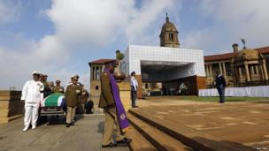 Military personnel carry the remains of the late Nelson Mandela at the Union Buildings in Pretoria, 11 December