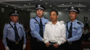 This picture taken on 22 September 2013 and released by Jinan Intermediate People's Court shows Chinese political star Bo Xilai (2nd R) wearing a pair of handcuffs as he stands in a courtroom in Jinan, east China's Shandong province