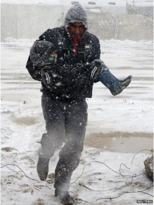 A man carrying a child runs for cover from the snow during a winter storm in Zahle town, in the Bekaa Valley December 11, 2013