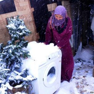 A Syrian refugee tries to move a washing machine outside her tent to protect it from snowfall at a makeshift camp in Terbol near the Bekaa Valley town of Zahleh in eastern Lebanon on December 11, 2013