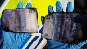 Police officer holds money found in a Lincolnshire waterway