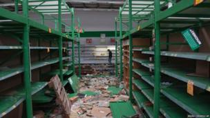 A shopkeeper inspects his store after it was looted in San Miguel de Tucuman, Argentina,