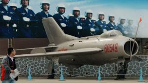 A man walks past a poster of Chinese airmen beside a Chinese-made J6 fighter jet on display at the People's Liberation Army Aviation Museum in Beijing on 4 December 2013