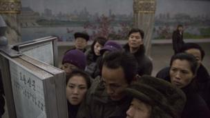 North Korean subway commuters gather around a public newspaper stand on the train platform in Pyongyang, North Korea, 13 December.