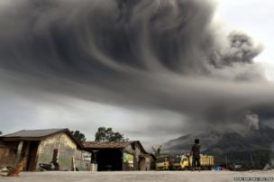 A woman looks on as Mount Sinabung spews ash, 18 November 2013