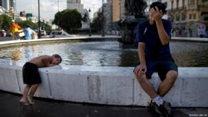 Daniel Britez endures the high temperatures as his son Alejandro, 4, cools down in a fountain in Buenos Aires, Argentina