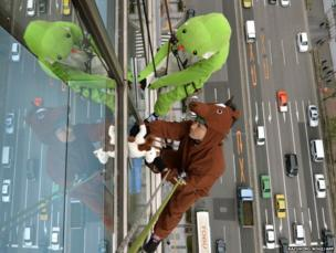 Workers clad in snake and horse costumes, to represent the outgoing Year of the Snake and incoming Year of the Horse, clean the windows of a hotel in Tokyo, Japan