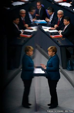 German Chancellor Angela Merkel is reflected in a glass barrier at the Bundestag in Berlin