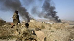 Afghan security forces watch burning Nato supply trucks after what police officials said was an attack by militants in the Torkham area near the Pakistani-Afghan border in Jalalabad Province (December 2013)