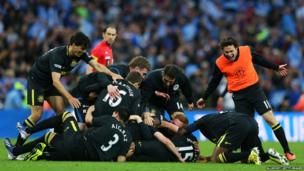 Wigan Athletic footballers celebrate on pitch