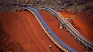 Worker walks near conveyer belts loaded with iron ore