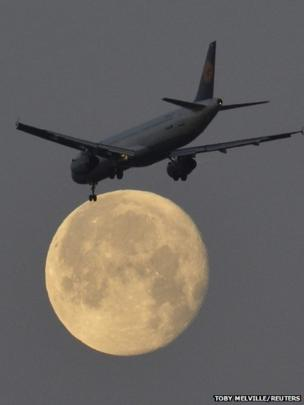 A passenger plane flies on its final descent to land with the moon seen behind at Heathrow Airport in London