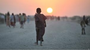 A Somali girl walking down a road at sunset at camp for displaced people near the town of Jowhar in southern Somalia on 14 December 2013
