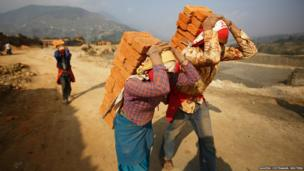 Workers carry bricks to load them into a truck before the delivery at a brick factory in Lalitpur