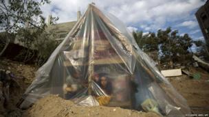 A Palestinian family in Beit Lahia sits in a tent