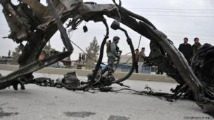 An Afghan policeman stands guard near the wreckage of a vehicle which was used in a suicide attack on the Kabul Jalalabad road, in Kabul on December 27, 2013