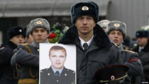 A police officer carries a portrait at the funeral of Russian police senior sergeant Dmitry Makovkin who was killed by a suicide bomb blast in Volgograd's main railway station