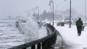 "A man jogs past waves crashing against the seawall around high tide during a winter nor""easter snowstorm in Lynn, Massachusetts January 2, 2014."
