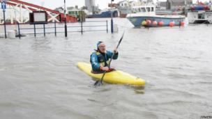 Man in kayak during floods in Ramsey, Isle of Man
